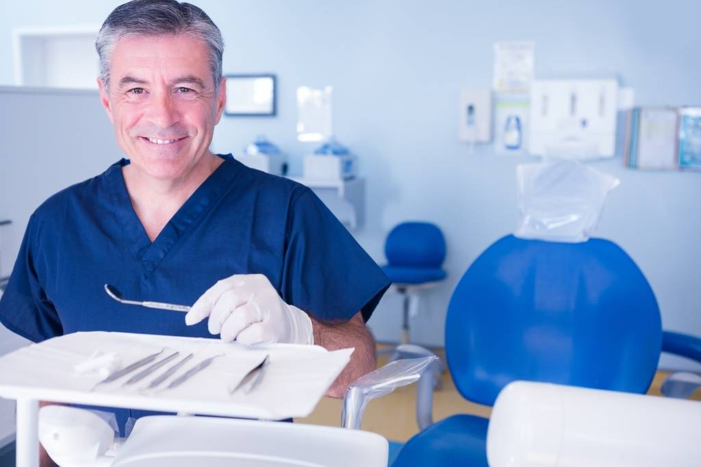 Dentist in blue scrubs smiling at camera holding tools