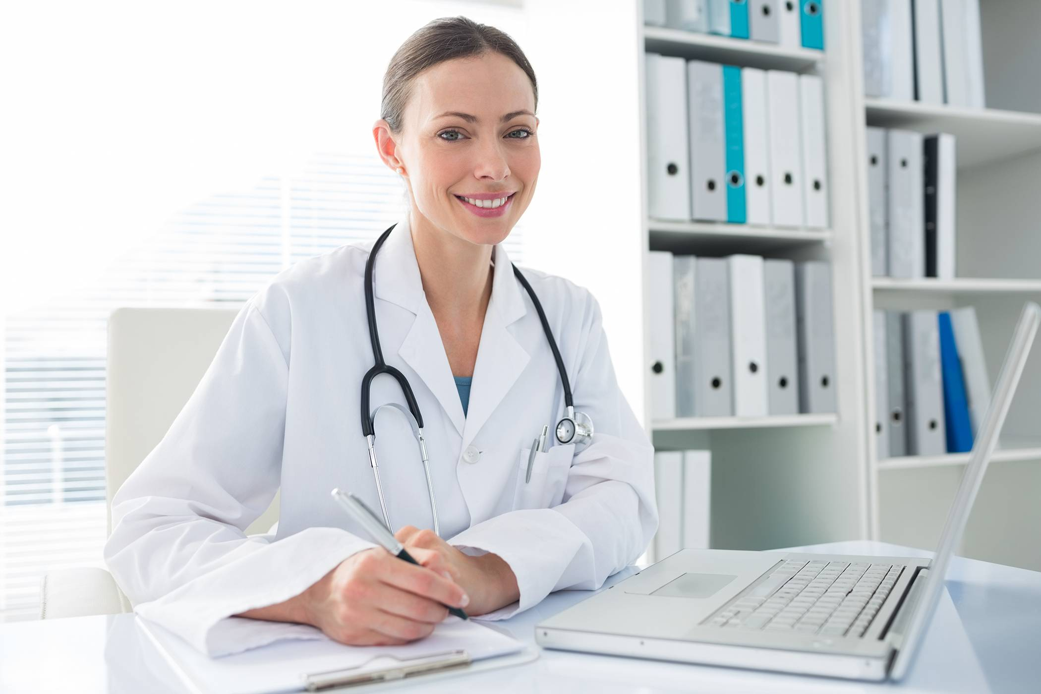 Beautiful female doctor with laptop and clipboard sitting at desk in clinic